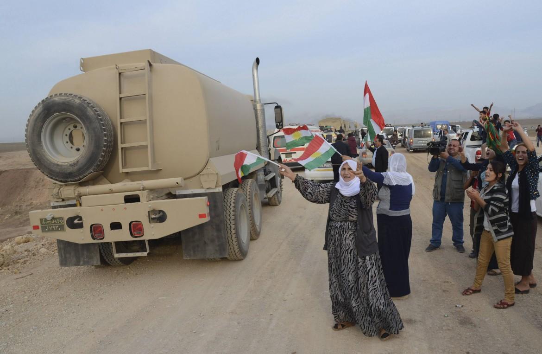 Un gruppo di peshmerga viene salutato dai kurdi a Suruc