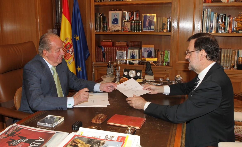 Il re Juan Carlos consegna il testo dell'abdicazione al premier Mariano Rajoy, in basso con il figlio Felipe