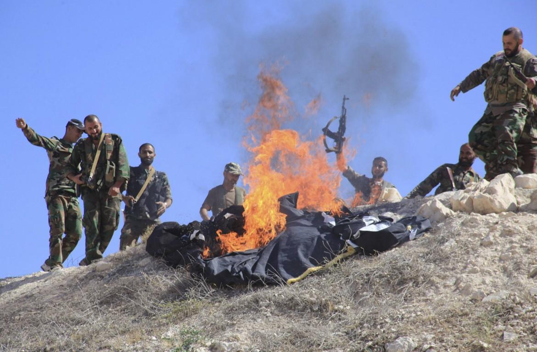 Una bandiera dello Stato Islamico data alle fiamme in Siria