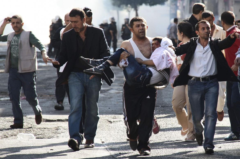 Manifestanti curdi trasportano i feriti degli scontri con la polizia turca