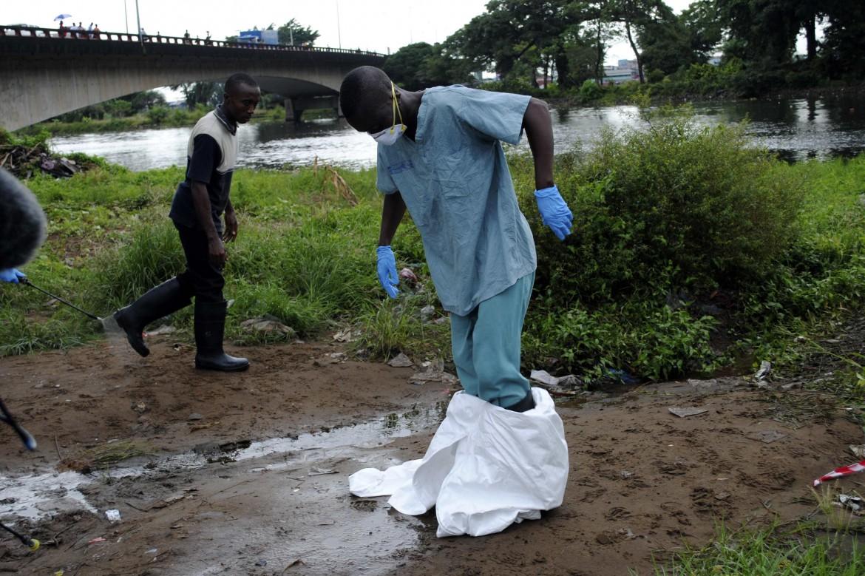 Monrovia, un operatore sanitario si toglie la tuta protettiva dopo averla irrorata di clorina