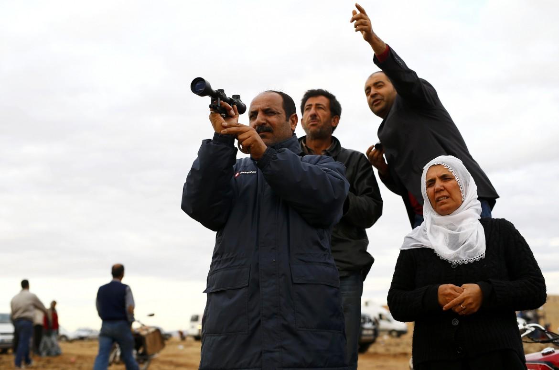 Kurdi osservano Kobane dal confine turco