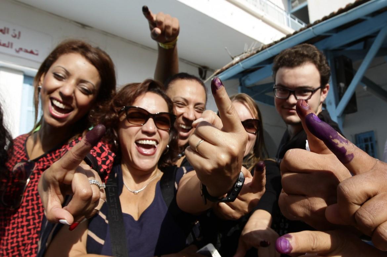 Elettrici tunisine mostrano il dito sporco d'inchiostro dopo il voto