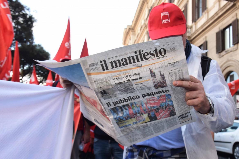 Un manifestante al corteo unitario dei sindacati dei lavoratori pubblici mentre legge il nostro giornale