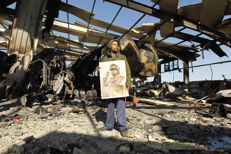 L'immagine di Gheddafi tra le macerie libiche