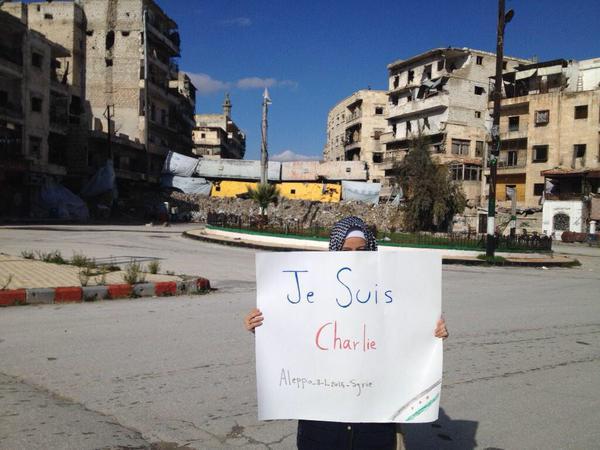 Una giovane manifesta per Charlie Hebdo in una piazza di Aleppo