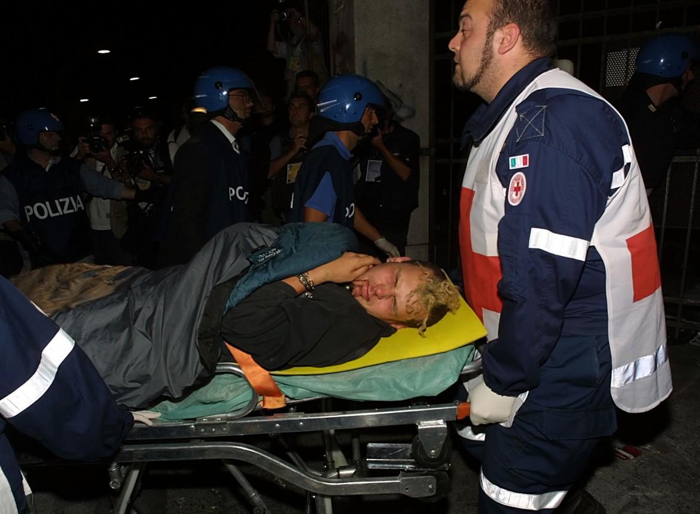 I feriti vengono trasportati fuori dalla Diaz, dopo l'irruzione della polizia. Genova 2001