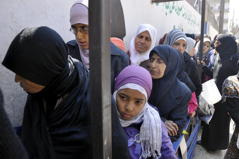 Donne in fila per il cibo nel campo palestinese di Yarmouk