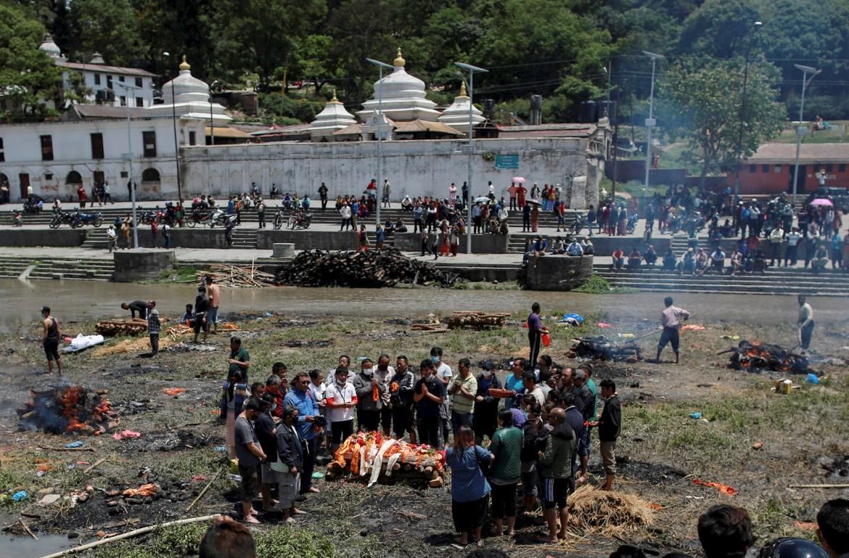 Folla celebra un funerale nei pressi di un fiume a Katmandu