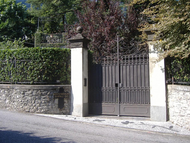 """Giulino di Mezzegra (CO) - Cancello di Villa Belmonte, oggi. Visibile la croce in legno """"Benito Mussolini, 28.4.1945"""""""