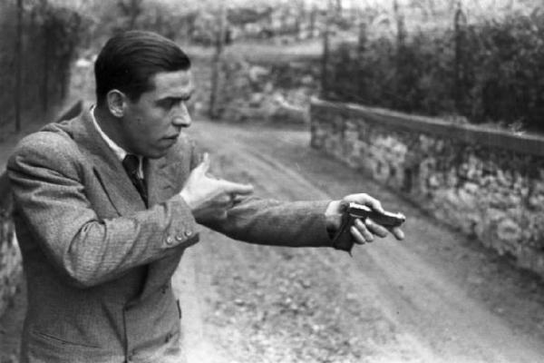 """Urbano Lazzaro """"Bill"""", il partigiano che arrestò Mussolini. Qui fotografato nell'inverno del 1945 davanti al cancello di villa Belmonte, mentre ricostruisce l'esecuzione di Mussolini, alla quale tuttavia non partecipò."""