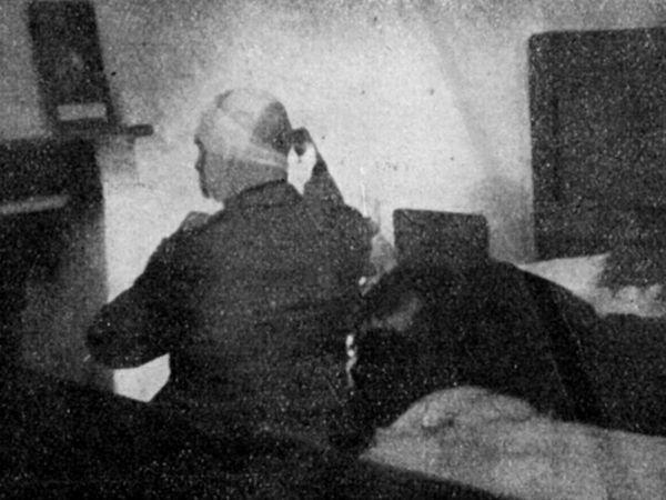 Fotografia di dubbia autenticità, ma utile come ricostruzione. Mussolini seduto sul letto della stanza di casa De Maria, 28 aprile 1945. Riconoscibile sul capo un inizio di fasciatura. L'altro corpo riverso sul letto corrisponderebbe a quello della Petacci, ma l'abbigliamento non corrisponde a quello di Piazzale Loreto. Se fosse autentica sarebbe l'ultima foto di Mussolini da vivo.