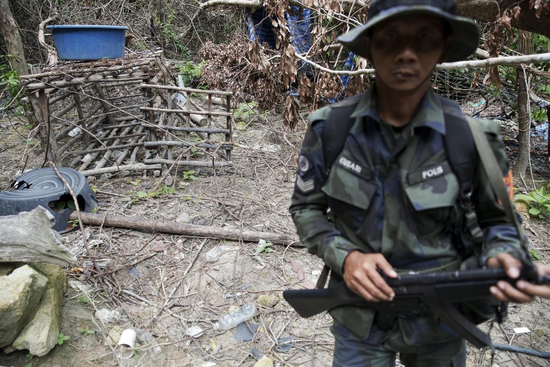La polizia malaysiana in uno dei campi riemersi dalla foresta