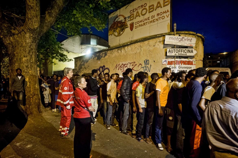 Migranti i fila alla distribuzione del pasto
