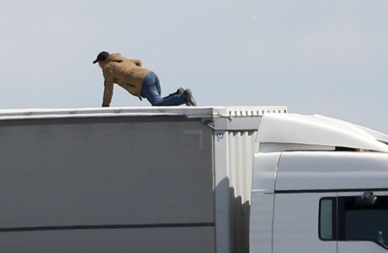 Un immigrato ceraca di salire su un Tir a Calais, in Francia