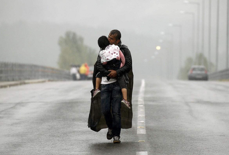 Idomeni, Grecia. Un rifugiato siriano avanza con il figlio sotto la pioggia verso il confine con la Macedonia