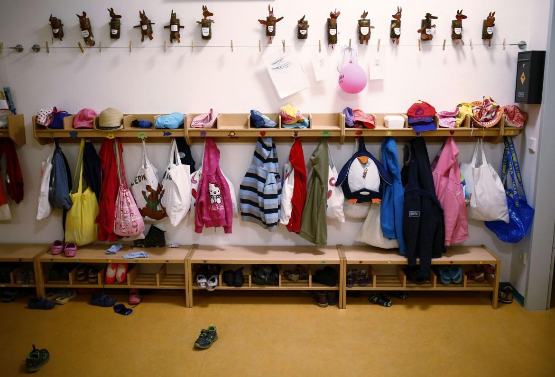 Gli attaccapanni dei bimbi all'ingresso di un'aula di un asilo nido