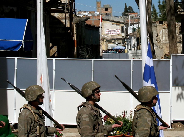 Soldati ciprioti di fronte a una sezione della barriera che divide in due Nicosia