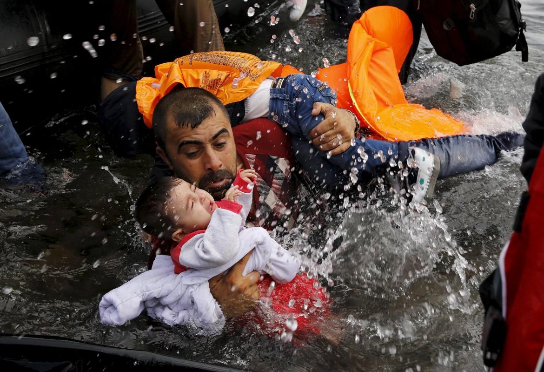Un padre siriano cerca di tenere a galla i propri figli dopo lo sbarco da un gommone a Lesbo il 24 settembre scorso