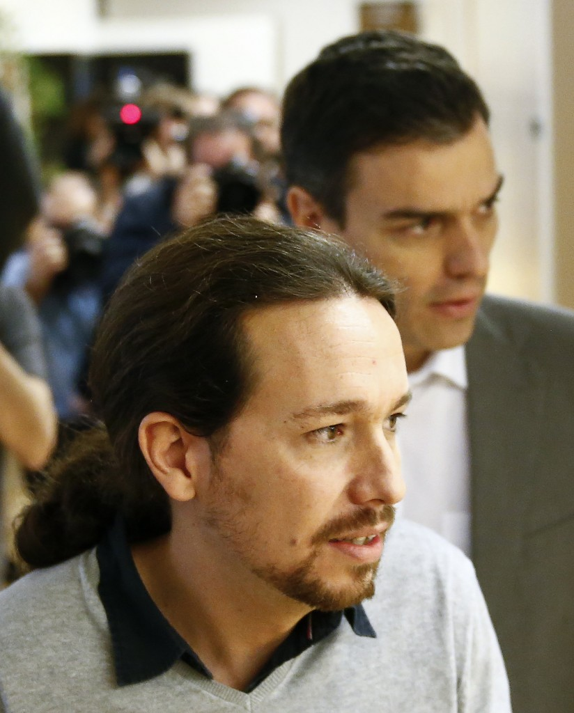 Il leader di Podemos Pablo Iglesias e dietro di lui Pedro Sánchez, segretario del Partito socialista spagnolo dal 2014