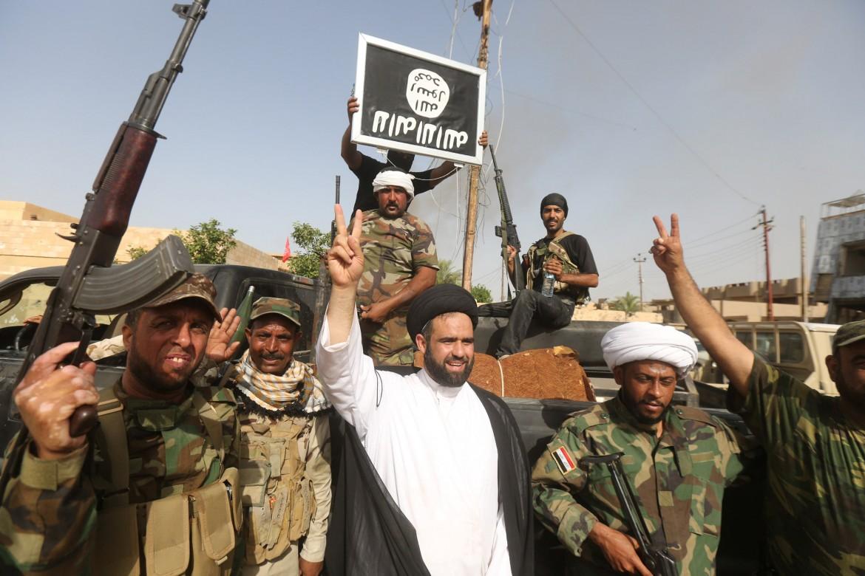 Soldati iracheni capovolgono la bandiera dell'Isis