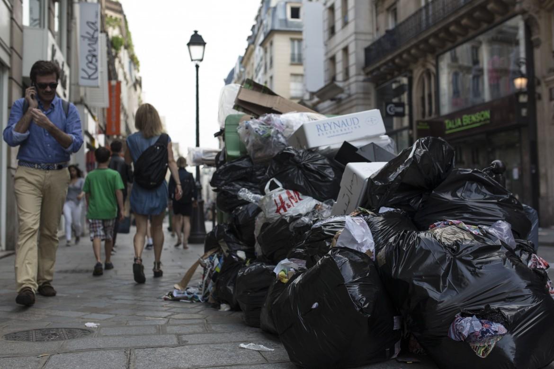 Parigi, l'immondizia lasciata in strada, nella foto piccola lo stadio Saint-Denis
