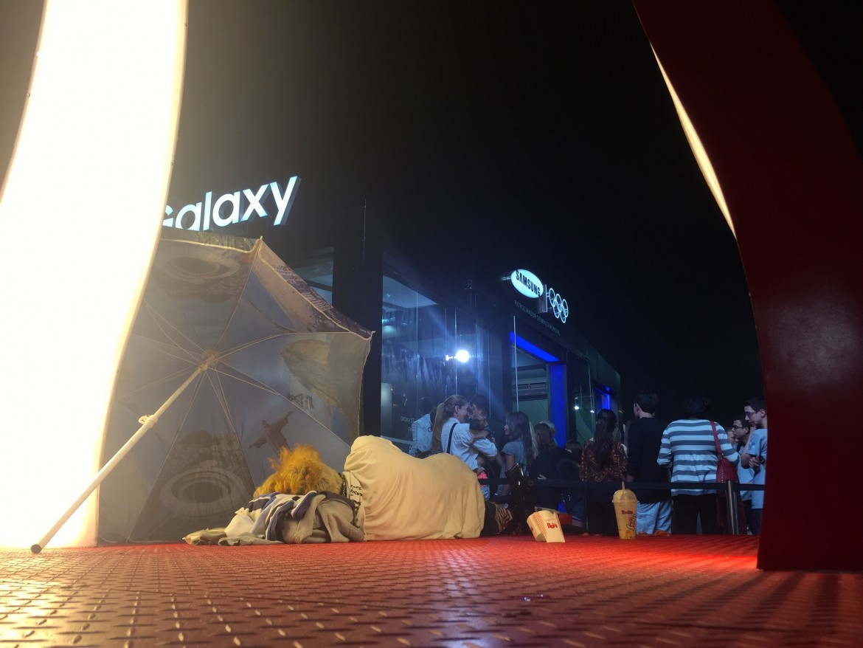 Scene che non si vedranno più durante i Giochi: un senzatetto dorme nello stand degli sponsor olimpici