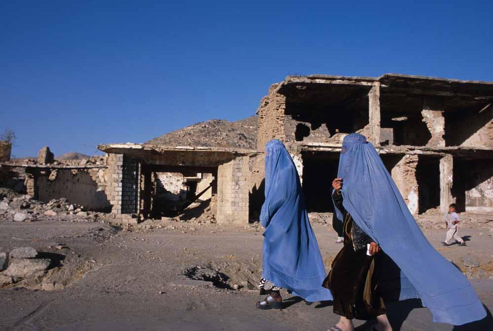 Due donne afgane di fronte alle macerie in un quartiere di Kabul, Afghanistan