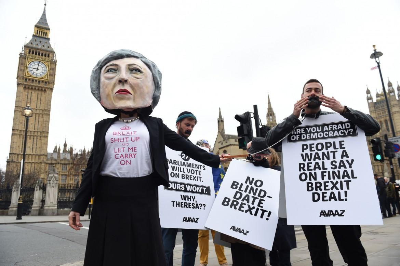 Protesta a Londra per l'uscita del Regno Unito dall'Ue; sotto la premier Theresa May firma la lettera del divorzio e la prima pagina di ieri del Guardian