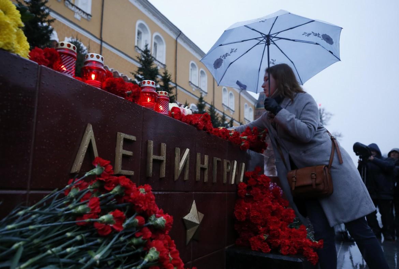 Fiori in omaggio alle vittime dell'attentato nella metro di San Pietroburgo; sotto il presidente russo Vladimir Putin