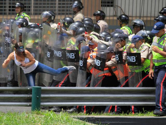 Caracas, una manifestante provoca la polizia
