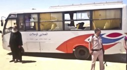 This image released by the Minya governorate media office shows a policeman and a priest next to a bus after stormed the bus in Minya, Egypt, Friday, May 26, 2017. Egyptian officials say dozens of people were killed and wounded in an attack by masked militants on a bus carrying Coptic Christians, including children, south of Cairo.  (Minya Governorate Media office via AP)