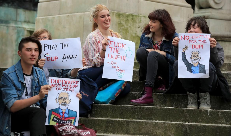 Liverpool, manifestazione contro l'accordo Tory-Dup; sotto Arlene Foster e Theresa May