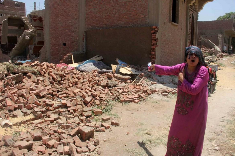 Una donna mostra una delle abitazioni già demolite a al-Warraq