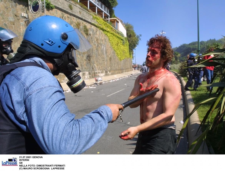 Un poliziotto e un manifestante durante i giorni del G8