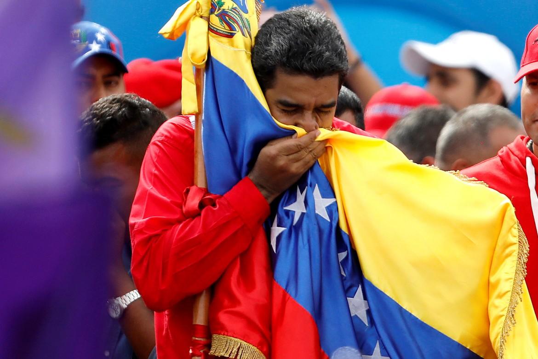 Il presidente venezuelano Maduro bacia la bandiera durante una cerimonia