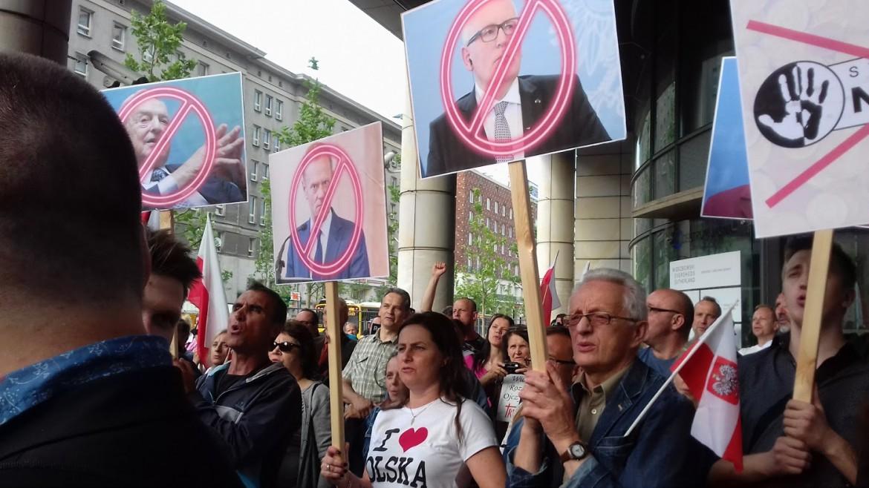 Varsavia, manifestazione nazionalista con cartelli contro George Soros (da sinistra), Donald Tusk, Jean-Claude Juncker e il logo di Never Again