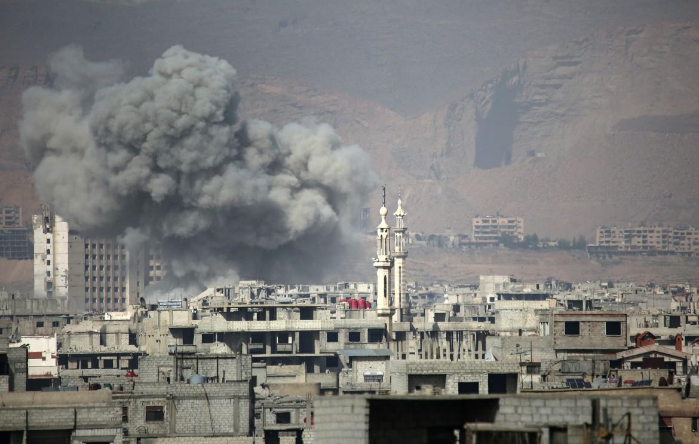 Una colonna di fumo si alza su Arbin, a Ghouta est, dopo un raid aereo del governo di Damasco