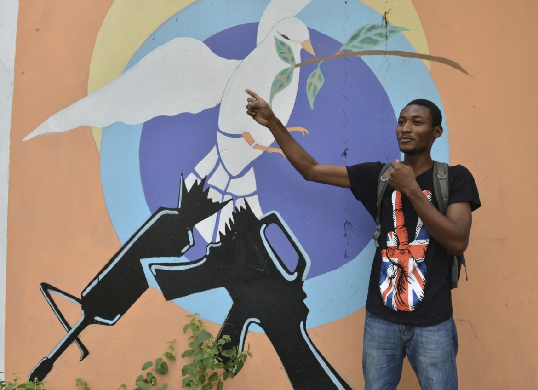 Tivoli Gardens, Kingston. Lo studente d'arte Jason Lorraine davanti al suo murale contro la violenza criminale