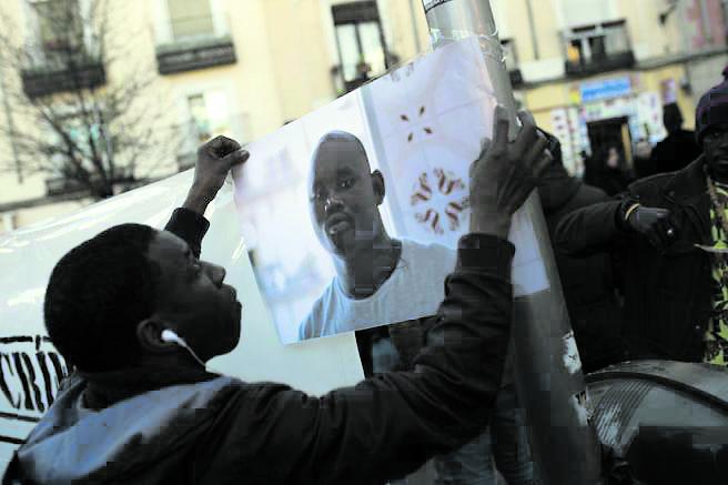 Manifestazione della comunità senegalese a Maddrid in memoria di Mame Mbaye. Sotto Arona Diakhate a terra