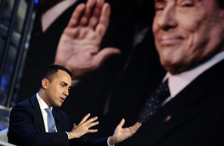 Luigi Di Maio in un talk, con la foto di Silvio Berlusconi sullo sfondo