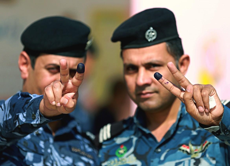 Due poliziotti iracheni mostrano il dito sporco di inchiostro: polizia ed esercito hanno votato giovedì