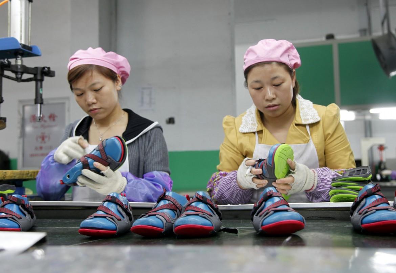 Lavoratrici cinesi in un'azienda che produce sandali
