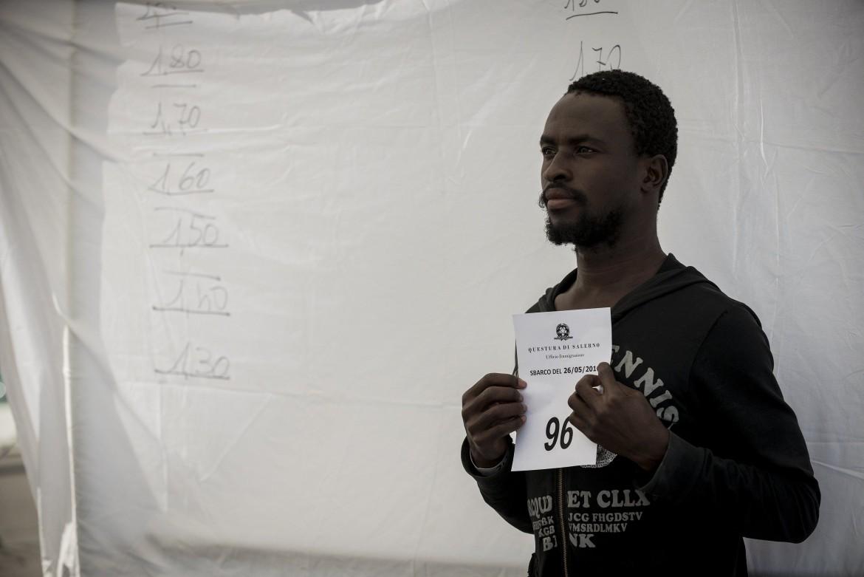 Un momento della prima identificazione di un migrante nel porto di Salerno