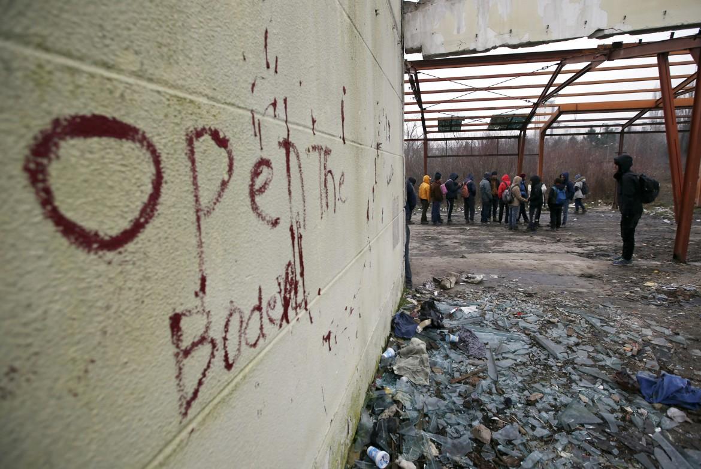 Migranti in fila per il cibo in una fabbrica abbandonata a Sid, in Serbia, vicino al confine con la Croazia