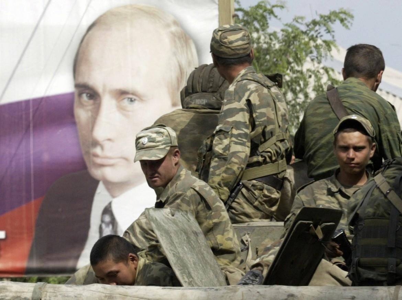 Truppe russe nel 2008 passano di fronte a un poster del presidente Putin a Tskhinvali, Sud Ossezia