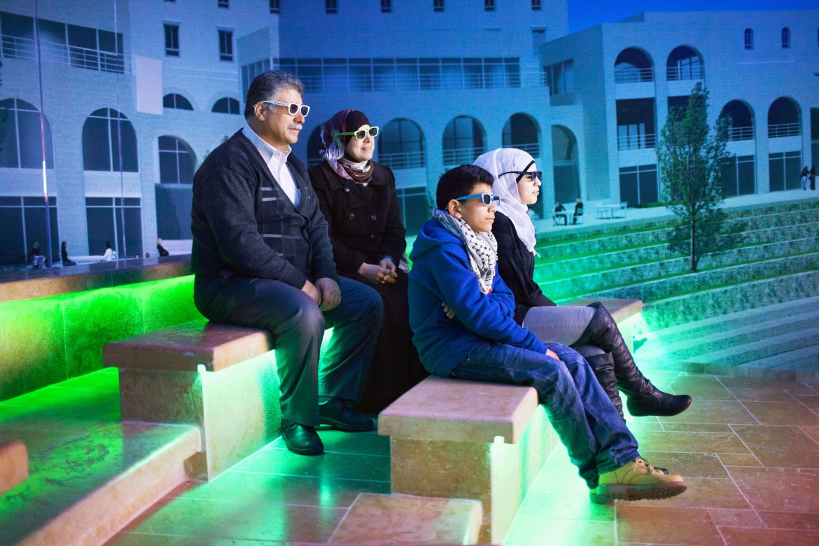 Andrea e Magda, 2013, A family is watching a promotional 3d video at the visitor center, The city