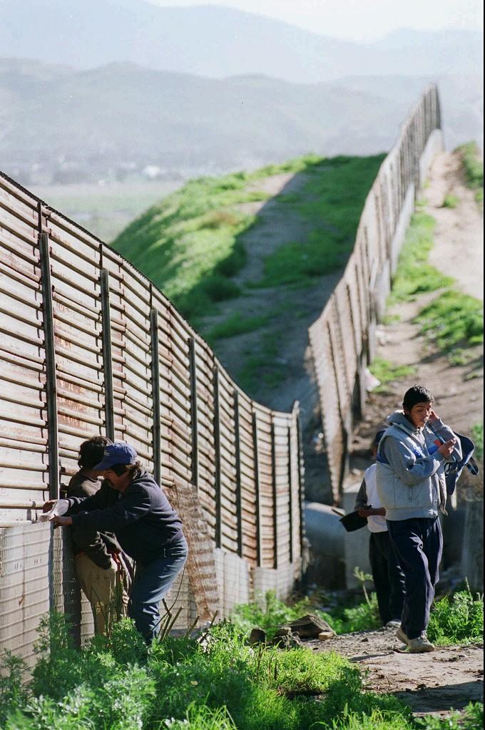 Cittadini messicani cercano di attraversare il muro con gli Usa nella zona di Tijuana