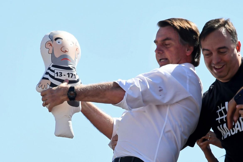 Bolsonaro, il candidato della destra, con un pupazzo di Lula