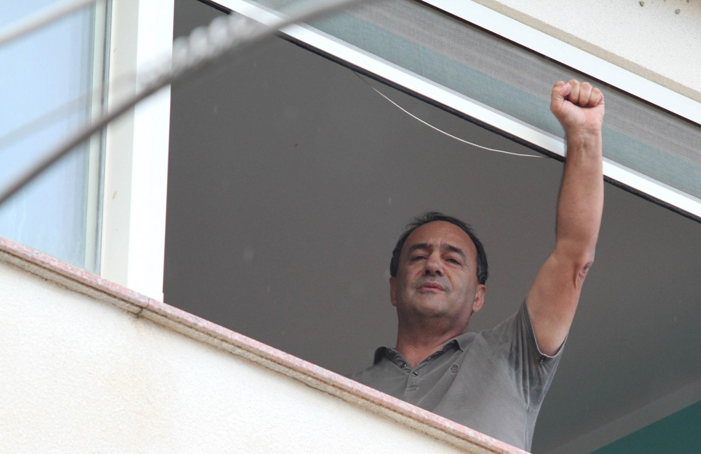 Il sindaco di Riace saluta la manifestazione a pugno chiuso da casa sua